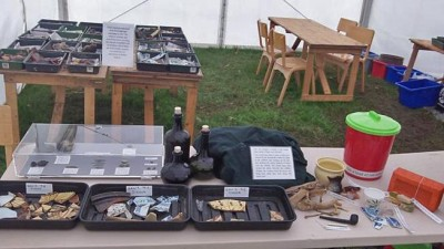 Figure 3: Finds and replicas on display with recently processed finds in trays at back (Image Copyright: Emily Rayner)